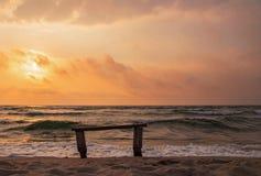 Eine einsame Bank in dem Meer im Sand auf dem Sonnenuntergang Lizenzfreies Stockfoto