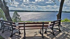 Eine einsame Bank, die den See, an einem sonnigen Tag des Sommers übersieht Stockfotos