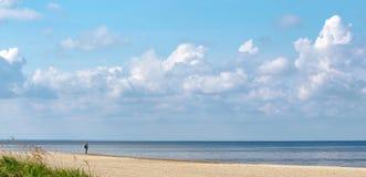 Eine einsame Frauenstellung auf dem Sand auf dem Ufer der Ostsee und des Betrachtens der Horizontlinie stockbild