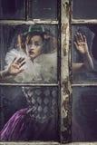 Eine einsame pierrot Frau hinter dem Glas Stockfotografie