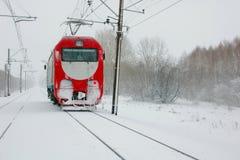 Eine einsame rote Lokomotive, die durch Blizzard rast Stockbilder