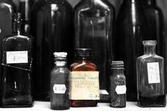 Eine einzelne braune Giftflasche auf einem Regal mit anderen Flaschen Stockbild