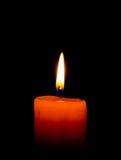 Eine einzelne brennende Kerze getrennt auf Schwarzem Stockbilder