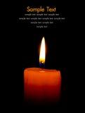 Eine einzelne brennende Kerze getrennt auf Schwarzem Lizenzfreie Stockfotografie