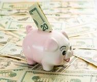 20 Dollarschein im Schlitz von piggy Bank Lizenzfreie Stockfotos