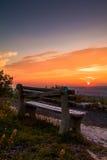 Eine einzige Bank betrachtet über dem Berg Sonnenuntergang Stockbilder