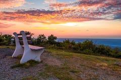Eine einzige Bank betrachtet über dem Berg Sonnenuntergang lizenzfreie stockfotografie