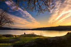 Eine einzige Frau sitzt durch Fjord bei Sonnenuntergang in Bergen stockfotografie