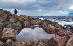 Eine einzige Zahl eines Fotografen mit einem Stativ auf einem steinigen Ozeanufer Lizenzfreie Stockbilder