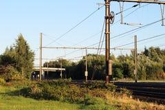 Eine Eisenbahn mit elektrischen Eisenbahnunterstützungen der Geländer unter den grünen Büschen Lizenzfreie Stockbilder