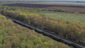 Eine Eisenbahnlinie, die durch den Wald und das Feld ?berschreitet Schie?en von einer H?he stock video footage