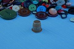 Eine Eisenmuffe und ein Stapel von farbigen Knöpfen auf dem Tisch Stockfotografie