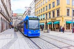 Eine elektrische Tram, die mit schönem Gebäude um Nationaltheater von München (Residenztheater, überschreitet) Stockfoto