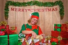 Eine Elfe, die Weihnachtsgeschenke auf den Nordpol einwickelt Lizenzfreie Stockbilder