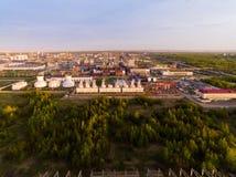Eine enorme Erdölraffinerie mit Rohren und Destillation des Komplexes auf einem grünen Feld umgeben durch Waldvogelperspektive Lizenzfreie Stockfotografie