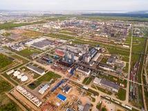 Eine enorme Erdölraffinerie mit Rohren und Destillation des Komplexes auf einem grünen Feld umgeben durch Waldvogelperspektive Stockbilder