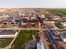 Eine enorme Erdölraffinerie mit Rohren und Destillation des Komplexes auf einem grünen Feld umgeben durch Waldvogelperspektive Lizenzfreies Stockbild