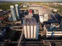 Eine enorme Erdölraffinerie mit Rohren und Destillation des Komplexes Schattenbild des kauernden Geschäftsmannes Lizenzfreies Stockfoto