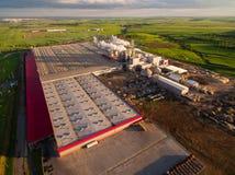 Eine enorme konkrete Anlage mit Rohren unter den Feldern Schattenbild des kauernden Geschäftsmannes Lizenzfreies Stockbild