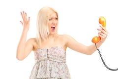 Eine entsetzte blonde Frau, die an einem Telefon schreit Lizenzfreie Stockfotos