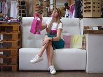 Eine erfüllte Frau, die auf einem Sofa nahe bei ihren Einkaufstaschen auf einem Speicherhintergrund sitzt Ein Mädchen mit einem s Lizenzfreie Stockfotos