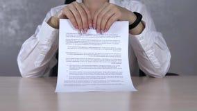Eine ernste Geschäftsfrau, die einen Vertrag in den Stücken zerreißt stock video