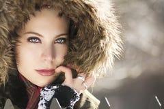 Eine erstaunliche blonde Frau mit dem Durchbohren von den blauen Augen, die eine Haube im Winter tragen Lizenzfreie Stockfotos
