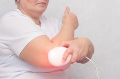 Eine erwachsene Frau behandelt das Ellbogengelenk mit einem Magnetfeld, entlastet die Schmerz und Entzündung mit einem medizinisc stockfotografie