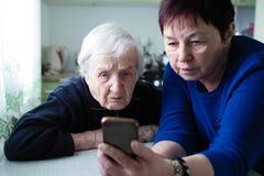 Eine erwachsene Frau zeigt einer alten Frau den Smartphoneschirm hilfe lizenzfreies stockfoto