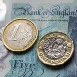 Eine Euromünze auf einer britischen fünf Pfund-Anmerkung in einem quadratischen Format Lizenzfreies Stockbild