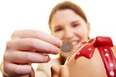 Eine Euromünze in der piggy Querneigung Lizenzfreies Stockfoto