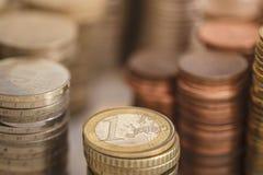 1 (eine) Euromünze zwischen anderen Währungen mit Goldhintergrund Lizenzfreie Stockfotografie