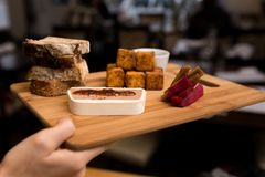 Eine europäische Artaperitifservierplatte, die hühnerleberkremeis, Polentastückchen, Brot und aus in Essig eingelegten Karotten b stockfotografie