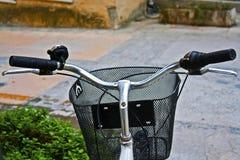 Eine Fahrradlenkstange mit Korb in einer bunten Straße Lizenzfreies Stockbild