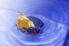 Eine fallende orange Scheibe in das Wasser nett Lizenzfreie Stockfotografie