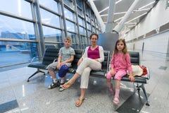 Eine Familie, die im Erholungsgebiet im Flughafen sitzt Stockfotos