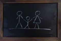 Eine Familie mit den Eltern und Kindern gezeichnet auf eine Tafel Stockbilder