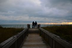 Eine Familie passt einen Sonnenaufgang am Strand auf lizenzfreies stockfoto