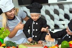 Eine Familie von Köchen Gesundes Essen Glückliche Familienmutter und -kinder bereitet Gemüsesalat in der Küche zu lizenzfreie stockbilder