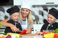 Eine Familie von Köchen Gesundes Essen Glückliche Familienmutter und -kinder bereitet Gemüsesalat in der Küche zu stockbilder