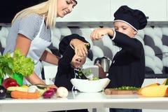 Eine Familie von Köchen Gesundes Essen Mutter und Kinder bereitet Gemüsesalat in der Küche zu stockfotos