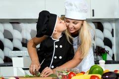 Eine Familie von Köchen Gesundes Essen Mutter und Sohn bereitet Gemüsesalat in der Küche zu stockbilder
