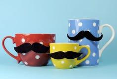 Eine Familie von Schnurrbärten auf blauem, rotem und gelbem Tupfenkaffee und den Teeschalen und -bechern Stockbilder