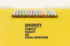 eine farbige Nachricht vor Graun Reihe des Mischungsfarbbleistifts auf gelbem Hintergrund mit Text Verschiedenartigkeit, Ethnie,  lizenzfreie stockfotografie