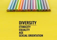 eine farbige Nachricht vor Graun Reihe des Mischungsfarbbleistifts auf gelbem Hintergrund mit Text Verschiedenartigkeit, Ethnie,  lizenzfreie stockbilder