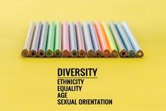 eine farbige Nachricht vor Graun Reihe des Mischungsfarbbleistifts auf gelbem Hintergrund mit Text Verschiedenartigkeit, Ethnie,  stockfotografie