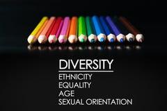 eine farbige Nachricht vor Graun Reihe des Mischungsfarbbleistifts auf schwarzem Hintergrund mit Text Verschiedenartigkeit, Ethni stockfoto