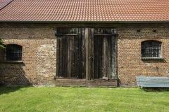 Eine Fassade einer alten Backsteinmauerscheune mit mit Ziegeln gedecktem Dach und Holztür stockfotografie