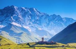 Eine faszinierende Ansicht über Ushguli-Dorf am Fuß von Schnee-mit einer Kappe bedeckt Stockbilder