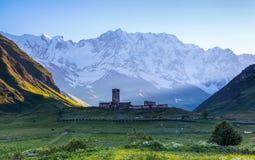 Eine faszinierende Ansicht über Ushguli-Dorf am Fuß von Schnee-mit einer Kappe bedeckt Lizenzfreies Stockbild